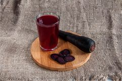 Carotte noire ou Salgam, scorsonère avec des glissières et un verre de son jus sur un fond blanc images stock