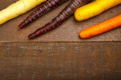 Carottes colorées fraîches sur la texture de bois dur Photos stock