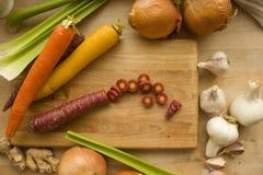 Carottes coupées en tranches entourées par des légumes Photographie stock