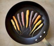 Carottes d'arc-en-ciel dans la casserole de torréfaction photos libres de droits