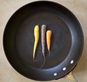 Carottes dans la grande casserole de torréfaction photos stock