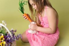Carottes de alimentation de fille au lapin de Pâques Photo libre de droits