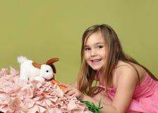 Carottes de alimentation de fille au lapin de Pâques Photos libres de droits