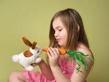 Carottes de alimentation de fille au lapin de Pâques Image stock