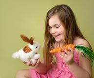 Carottes de alimentation de fille au lapin de Pâques Photographie stock