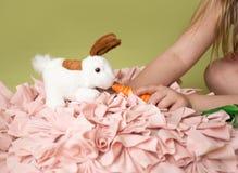 Carottes de alimentation de fille au lapin de Pâques Photo stock