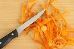 Carottes et couteau de peau Image stock