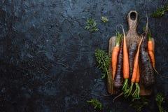 Carottes organiques moissonnées fraîches sur la planche à découper en bois sur la vue supérieure de fond noir photos stock
