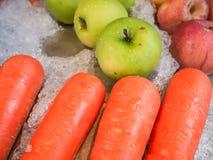Carottes, pommes, pommes vertes sur la glace de fruit image stock