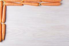 Carottes sur un fond en bois Images stock