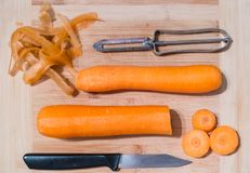 Carottes, un couteau et une éplucheuse végétale sur un hachoir en bois Photos libres de droits