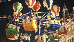 Carousel against dark night sky on the Red Square. Lights of State Department Store on a background. stock footage