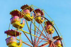 Carousel ferris wheel against a blue sky Stock Images
