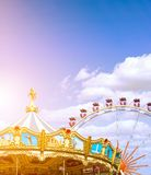 Carousel and ferris wheel in the park. Summer fun for the whole family. Good rest. Extreme. Sun rays. Space for text Stock Images
