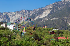 Carousel Ferris wheel in sunny Yalta on the background of the Crimean mountains Royalty Free Stock Photo
