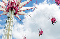 Carousel with flying people on pink seats Stock Image
