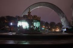 Carousel in the fog in historical place People`s Friendship Arch in city Kiev. royalty free stock images