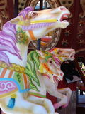 Carousel horses. A profile of three carousel horse heads, vertically shot. In the background is a little of the carousel. One horse features lavender and white stock photography