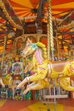 Carousel horses 2. Garish painted fair ride with horses on golden poles stock photo