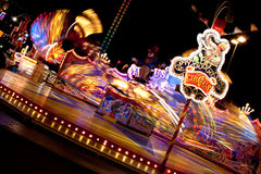 Carousel at night. A moving carousel at night with motion blur of colorful lights stock photo