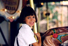 Carousel Ride Tara scan03. Young child riding on a carousel and smiling at the camera Royalty Free Stock Photo