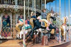 Caroussel hamn Honfleur med två små flickor som rider en häst Royaltyfri Bild