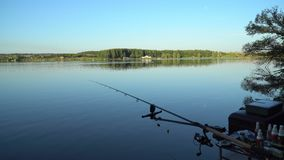 Carp fishing on pond. Carp fishing equipment and rubber boat near wooden pier on pond stock video