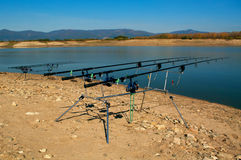 Carp fishing. Two angling scene. Looking along three carp rods towards a pond. Stock Photos