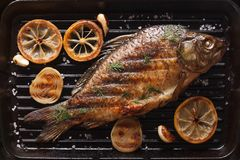 Carp with lemon, onion and spices on a black grill pan, top view Stock Photography