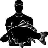 Carp. Silhouette of fisherman holding big carp fish Royalty Free Stock Photography