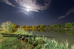 Carp spinning reel angling rods on pod standing. Night Fishing, Carp Rods, Cloudscape Full moon over lake. Royalty Free Stock Photo