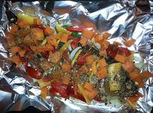 Carp with vegetables on foil Stock Photography