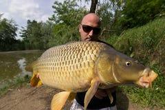 Carpa e pescador, troféu da pesca da carpa fotografia de stock