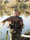 Carpa a specchi del pesce di With del pescatore Pescando sull'autunno Immagine Stock
