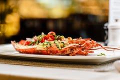carpaccio烹调非常好的食物意大利生活方式豪华 在一半烘烤和切的整个龙虾服务用蕃茄沙拉和调味汁在白色板材 免版税库存照片