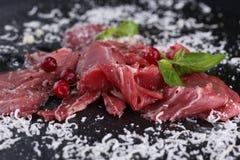 Carpaccio βόειου κρέατος με το τυρί παρμεζάνας και πράσινα στο μαύρο υπόβαθρο Στοκ Φωτογραφίες