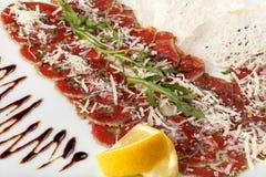 Carpaccio βόειου κρέατος με το arugula και το λεμόνι, την παρμεζάνα και τη σάλτσα Στοκ Εικόνες