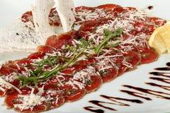 Carpaccio βόειου κρέατος με το arugula και το λεμόνι, την παρμεζάνα και τη σάλτσα Στοκ Φωτογραφία