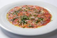 Carpaccio βόειου κρέατος που εξυπηρετείται με το ruccola σε ένα άσπρο πιάτο στοκ εικόνες με δικαίωμα ελεύθερης χρήσης