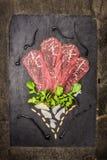 Carpaccio βόειου κρέατος που συνθέτει με την παρμεζάνα, arugula, καρύδια πεύκων και βαλσαμικός στη σκοτεινή πλάκα Στοκ εικόνα με δικαίωμα ελεύθερης χρήσης