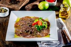 Carpaccio βόειου κρέατος στο άσπρο πιάτο, ξύλινο υπόβαθρο κλείστε επάνω Στοκ Εικόνες