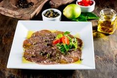 Carpaccio βόειου κρέατος στο άσπρο πιάτο, ξύλινο υπόβαθρο κλείστε επάνω Στοκ Φωτογραφίες