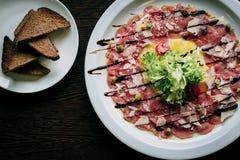 Carpaccio του μοσχαρίσιου κρέατος σε ένα άσπρο πιάτο Στοκ φωτογραφία με δικαίωμα ελεύθερης χρήσης