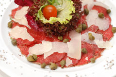Carpaccio. Made of raw beef slices with parmesan and capers served at restaurant stock photos