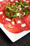 Carpaccio. On a plate with parmesan and pignolia royalty free stock photo