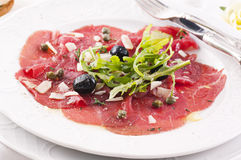 Carpaccio. With olives and parmesan royalty free stock photos