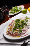 Carpaccio. Dish of raw meat marinade with oil, lemon juice, salt and pepper royalty free stock photos