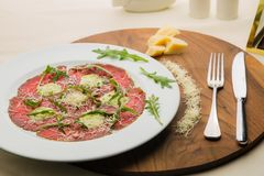 Carpaccio with arugula in restaurant. Served plate with carpaccio with arugula on a white plate in restaurant. Delicious italian meal for lunch or dinner stock photography