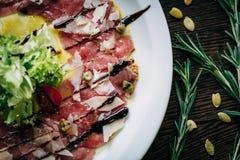 Carpaccio av kalvköttet i en vit platta Arkivbilder