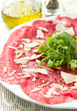 Carpaccio of beef on arugula Royalty Free Stock Image